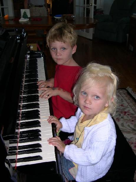 Photo of Lily and Charles playing the piano.